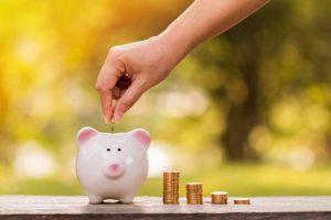 Man putting coin in a piggy bank