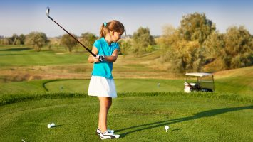 A girl about to strike a golf ball