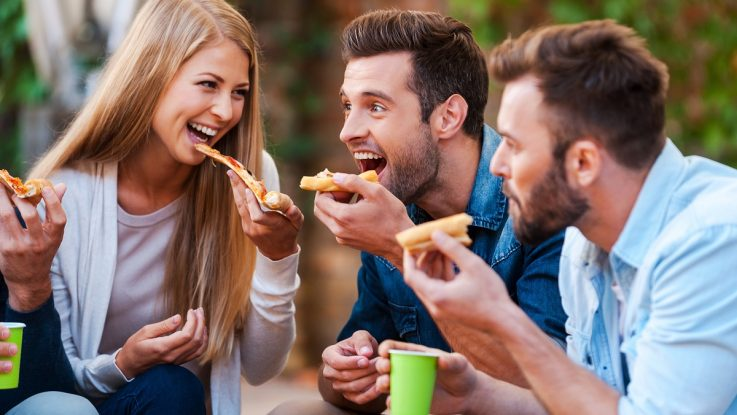 Happy friends eating pizza