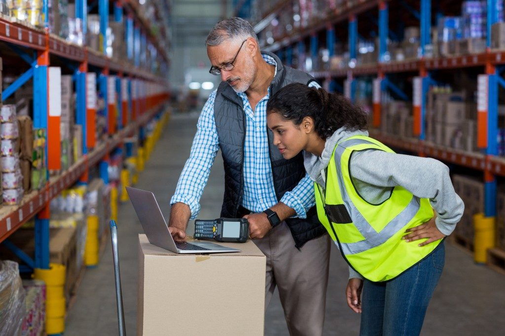 Manager and worker discussing at the packaging warehouse
