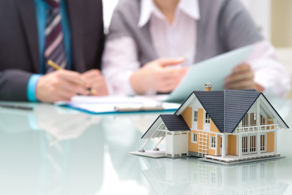 Model house with couple signing mortgage contract