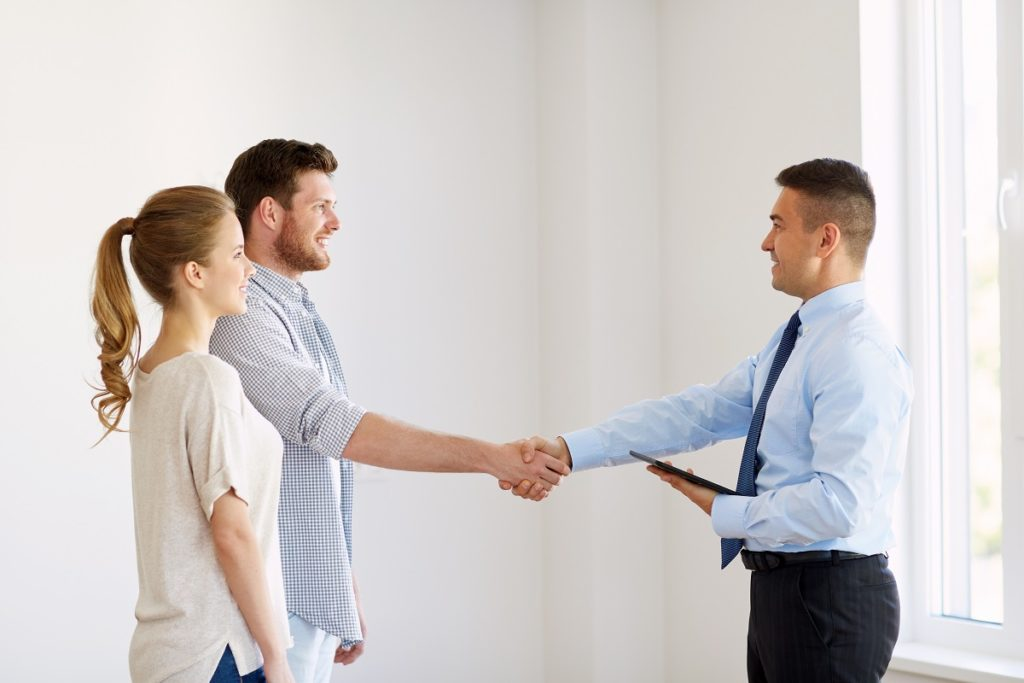 Real estate agent and clients shaking hands