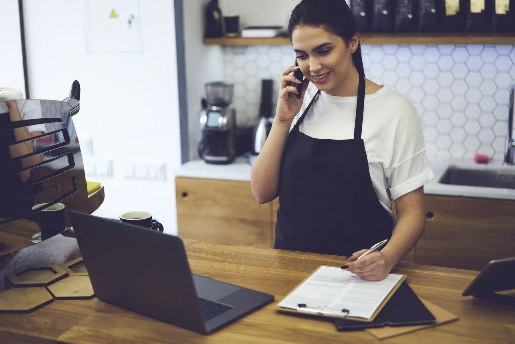 entrepreneur dressed in black apron with mock up making coffee business by herself.
