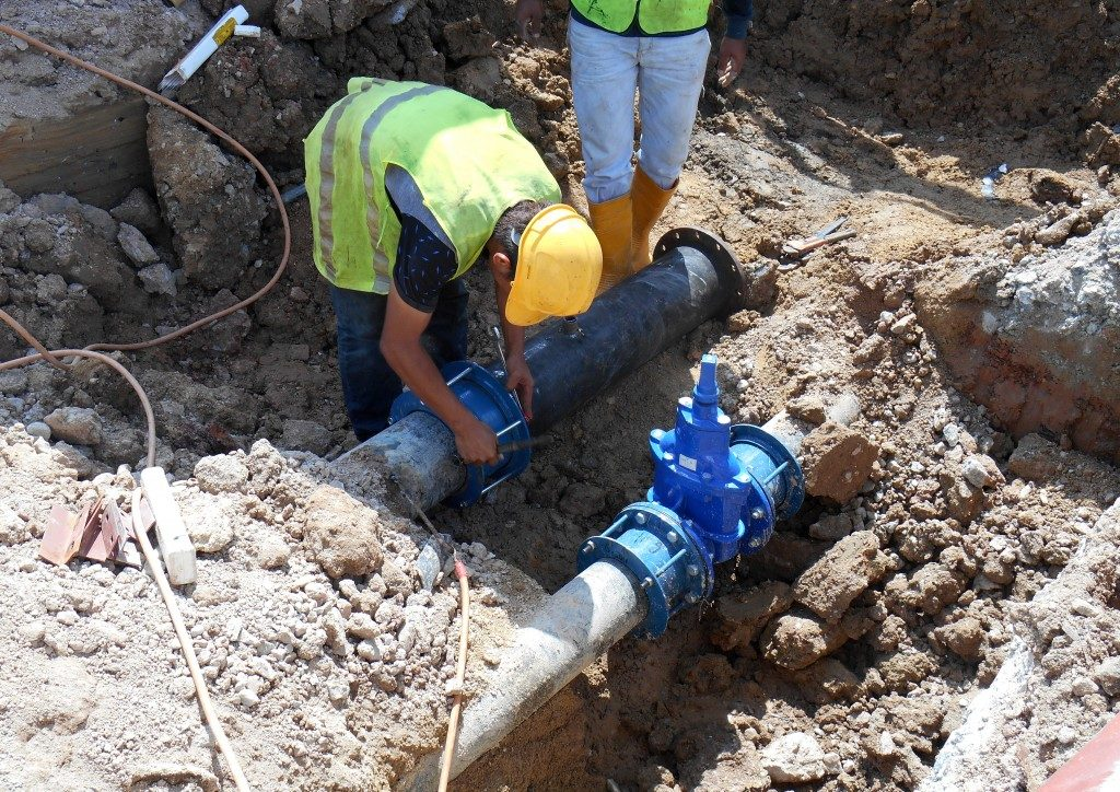 Workers installing sewage pipes