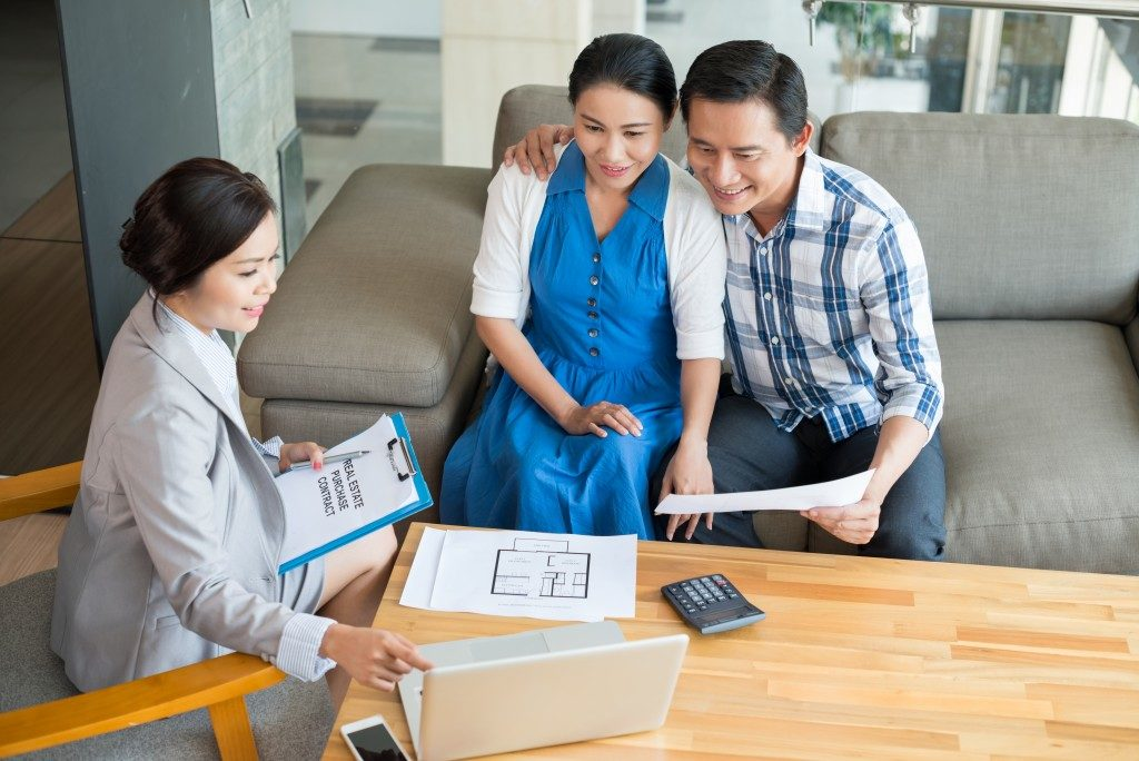 asian couple talking to a businesswoman
