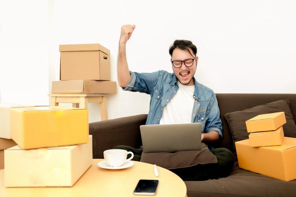 Man celebrating while looking at laptop