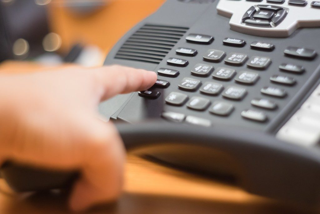 Businessman dialing the voip phone