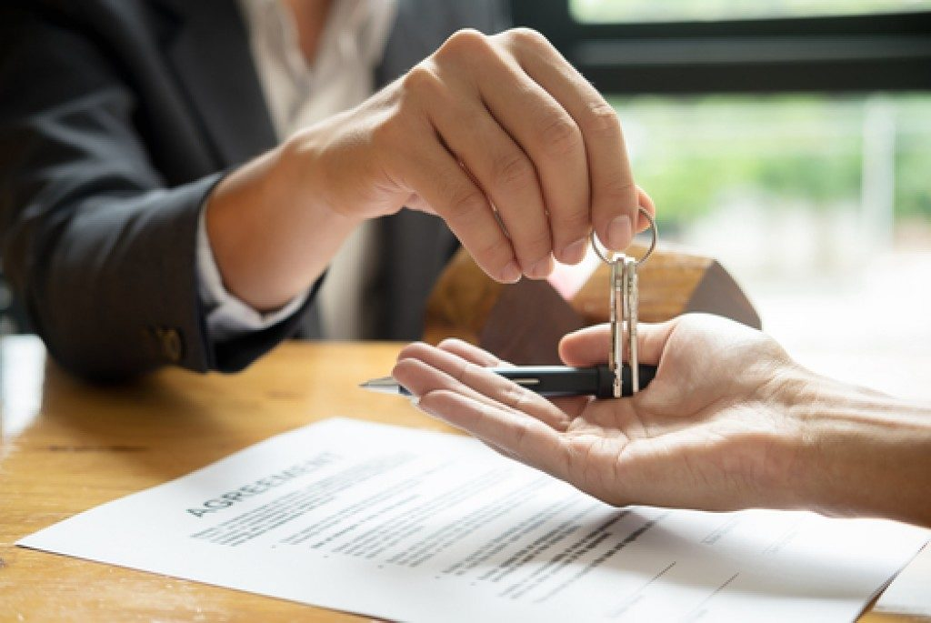 Real estate agent handing house keys to client