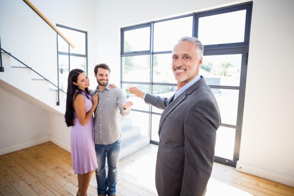 Couple receiving house keys from broker