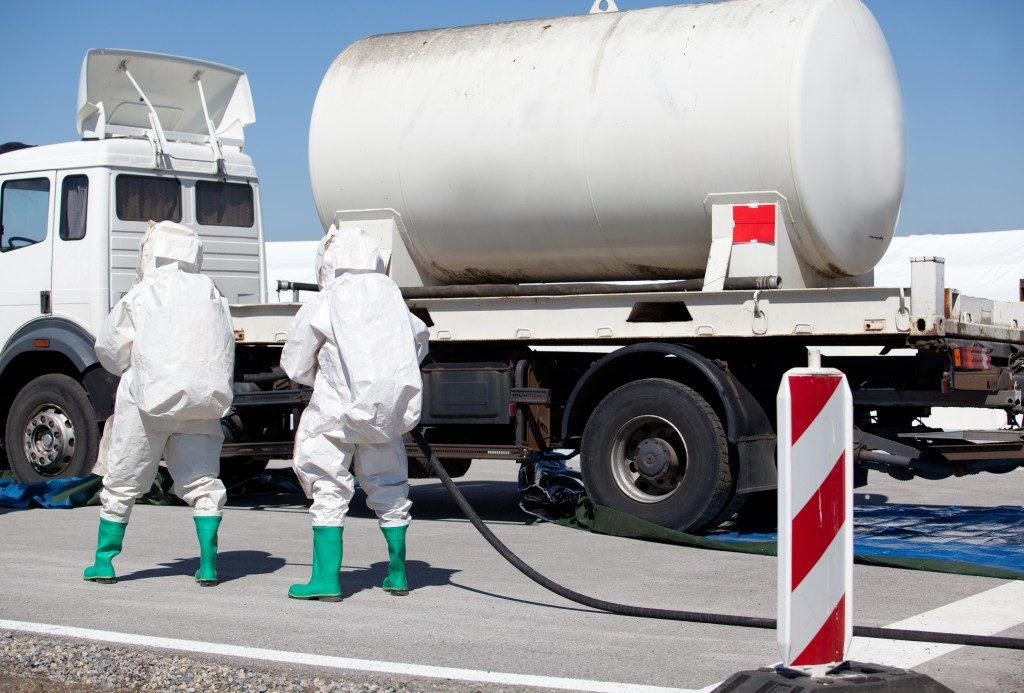 two men in safety uniform checking on the truck transporting chemical