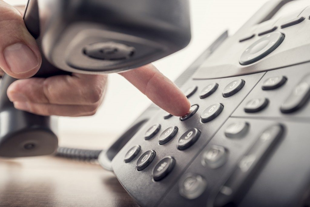 Person trying to make a call using the landline