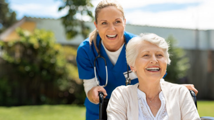 Elderly woman in wheelchair with nurse