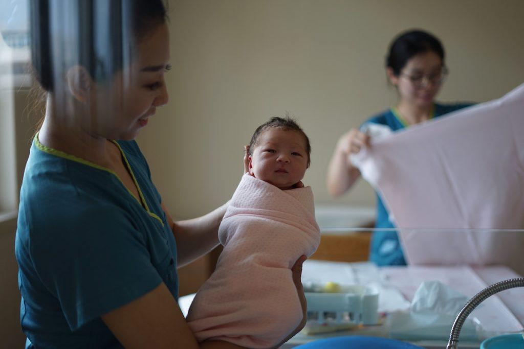 nurse holding a newborn baby