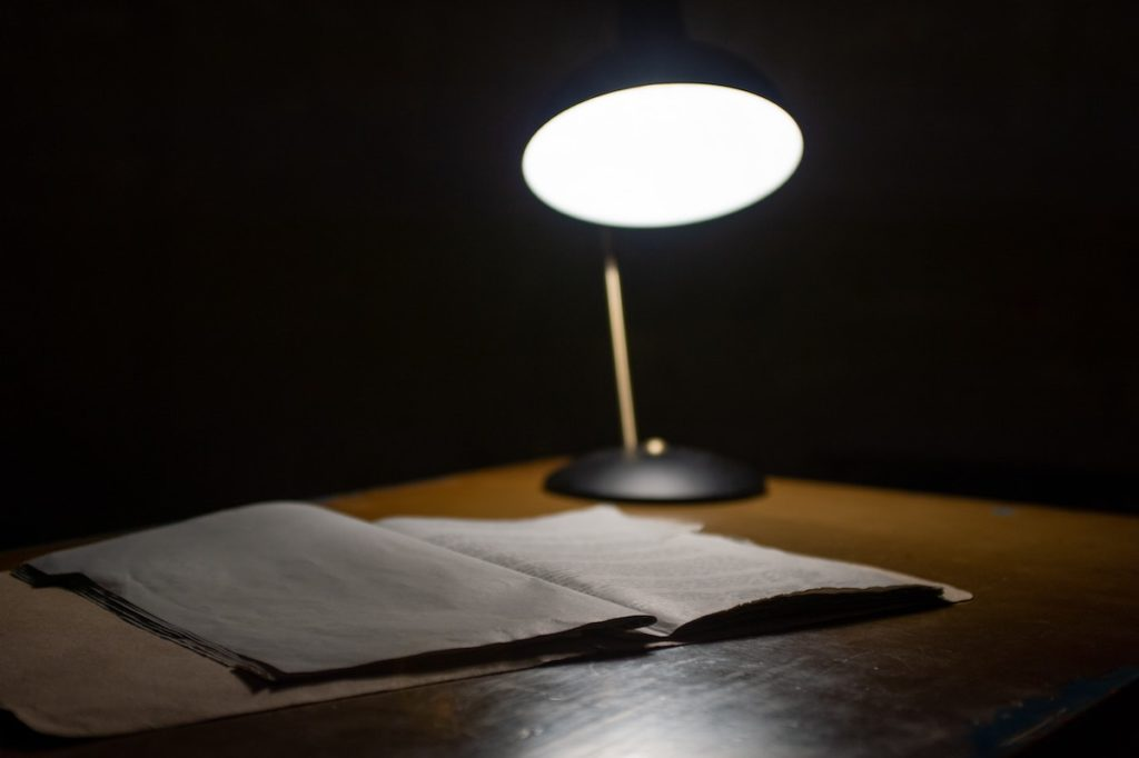 light from lamp shining on notebook